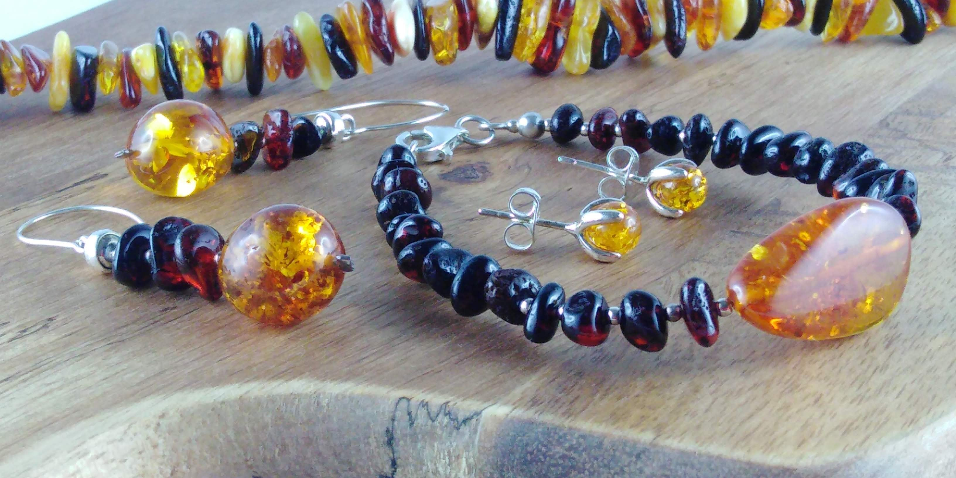 Baltic amber necklace, earrings and bracelet in sterling silver on flat wood board